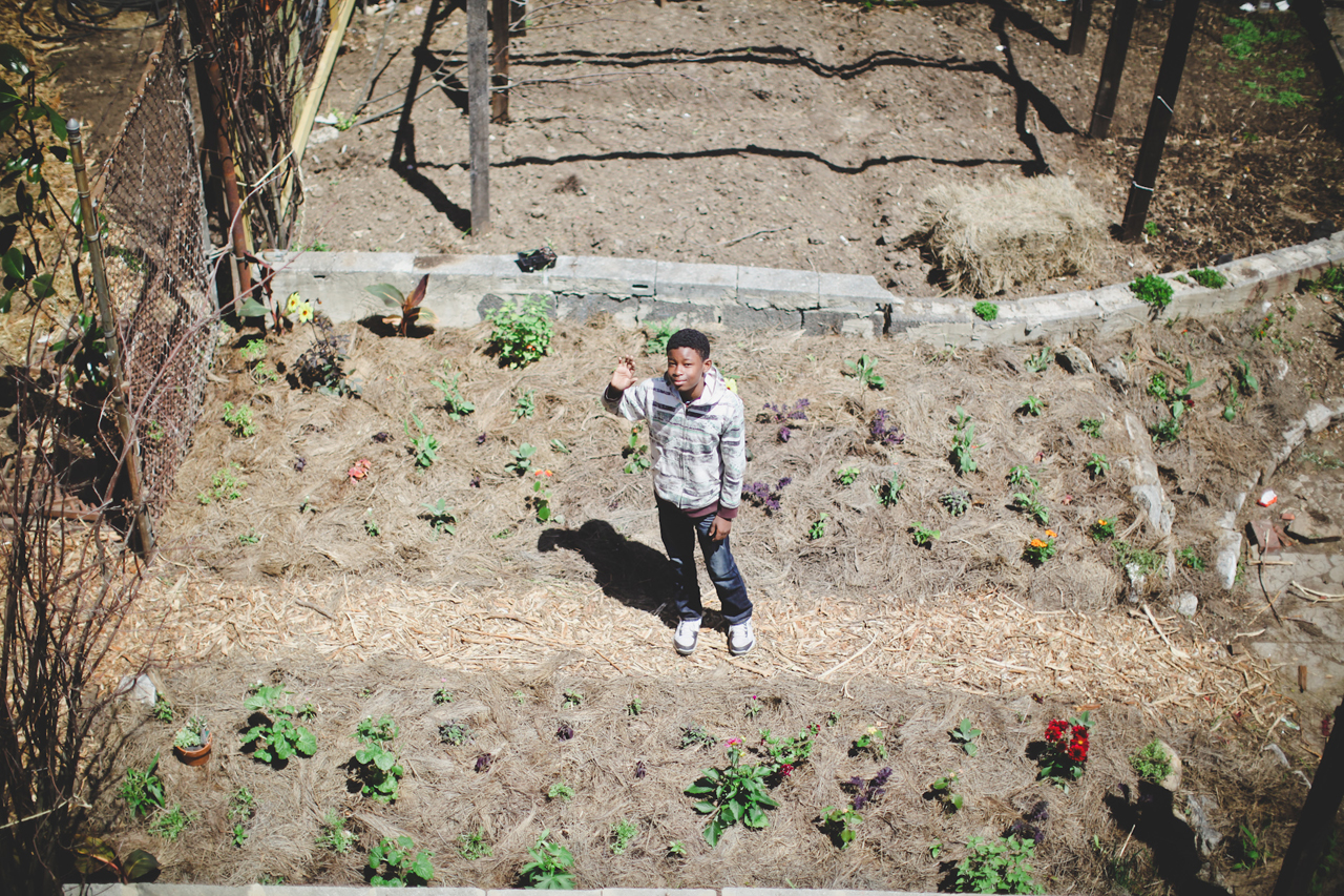 Junior Gardener Yahya Jr. waves along the pathway to our new cut flower space.